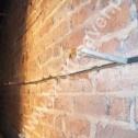Naprawa muru z cegły. Widoczne kliny stabilizujące profile śrubowe Brutt'a w czasie wstępnego wiązania zaprawy Saver Powder.