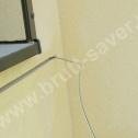 """Przymiarka """"na sucho"""" śrubowych profili Brutt Saver. Widoczna, zagięta końcówka Saver Profilu wprowadzone do otworu wywierconego w murze (kotwienie końcówki)."""