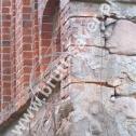 Wzmocnienie popękanych murów kamiennego kościoła z wykorzystaniem Saver Profili. Widoczny montaż profili w spoinach pomiędzy kamieniami (oplatanie kamienia).