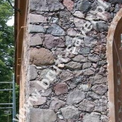 Montaż spiralnych Saver Profili w obiekcie z kamienia bezpośrednio w wyczyszczonych spoinach pomiędzy ich poszczególnymi warstwami. Widoczne m.in. kliny stabilizujące profile na czas wstępnego wiązania zaprawy Saver Powder.